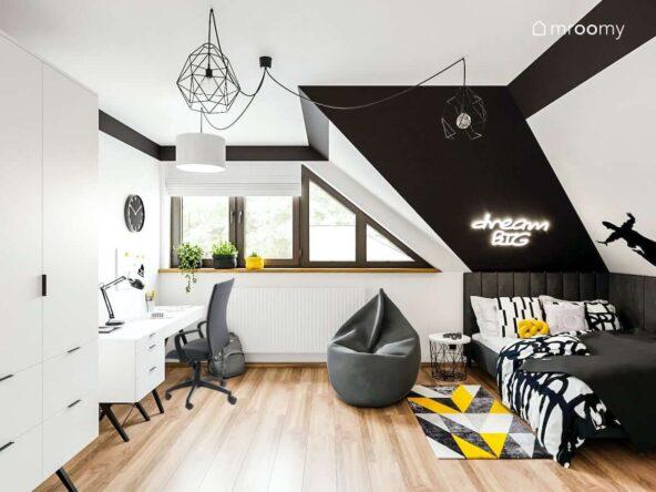 Czarno biały pokój dla nastolatki z biurkiem szafą oraz szarą pufą i kolorowym dywanem oraz świecącym napisem na ścianie