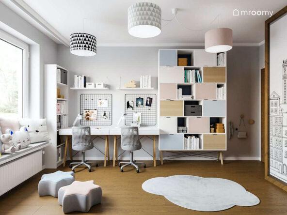 Strefa nauki z dwoma biurkami i pojemnymi regałami w pokoju dla rodzeństwa na podłodze dywan w kształcie chmurki i pufki gwiazdki