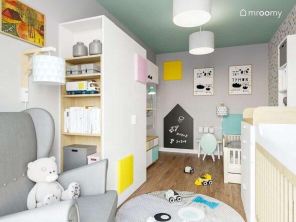 Pokoik rodzeństwa utrzymany w delikatnych pastelowych kolorach z dużą białą szafą drewnianymi łóżeczkami szarym fotelem i tablicą magnetyczną na ścianie