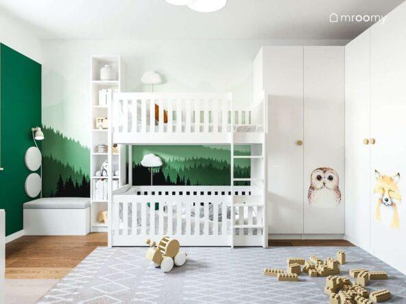Tapeta przedstawiająca las oraz naklejki zwierzęta na dużej szafie w umeblowanym na biało pokoju dla rodzeństwa