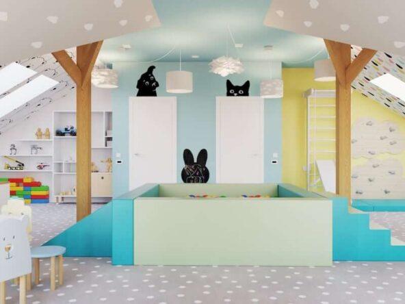 Poddaszowa bawialnia dla dwóch chłopców z suchym basenem z kulkami drabinką gimnastyczną i ścianką wspinaczkową a także z kolorowymi ścianami i naklejkami z psem i kotem nad drzwiami