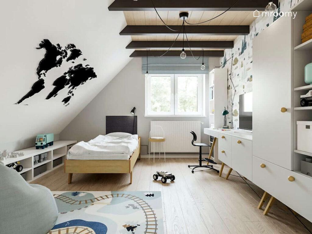 Jasny pokój dla chłopca z łóżkiem ze sklejki pod skosem z jasnoszarymi meblami z dodatkami w kolorze naturalnego drewna z czarnym krzesłem obrotowym magnetyczną mapą świata na ścianie czarnymi dodatkami czarnymi belkami na suficie roletą rzymską w kolorze szaro-niebieskim