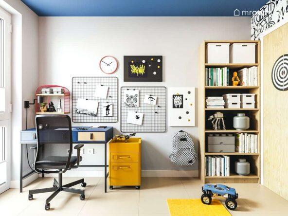 Pokój młodzieżowy dla chłopca utrzymany w kolorystyce żółto czarno granatowej z biurkiem w stylu loftowym z kontrastowym żółtym kontenerkiem biurowym i metalowymi tablicami na notatki