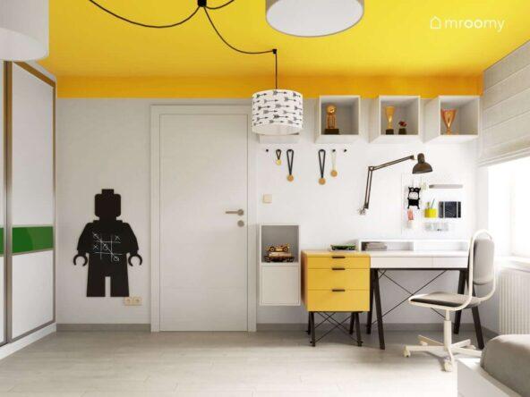 Pokój dla nastoletniego sportowca i fana gier komputerowych w kolorystyce biało-żółtej z czarnymi dodatkami z żółtym sufitem i nowoczesnym biurkiem skandynawskim