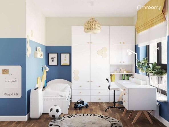 Białe łóżko duża szafa i kilka kwietników w małym pokoju dla chłopca ze ścianami ozdobionymi plakatami w ramkach i panelami w kształcie heksagonów