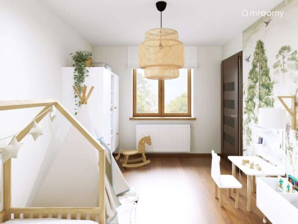 Leśny pokój dla małego chłopca w którym dominują białe oraz drewniane meble a na suficie wisi bambusowa lampa