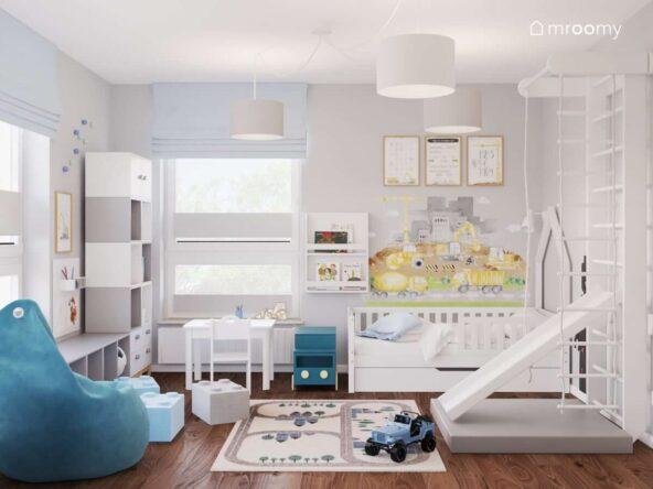 Pokój małego chłopca z białym łóżkiem białymi i szarymi półkami białą drabinką gimnastyczną ze zjeżdżalnią a także ścianą ozdobioną naklejką z motywem budowy