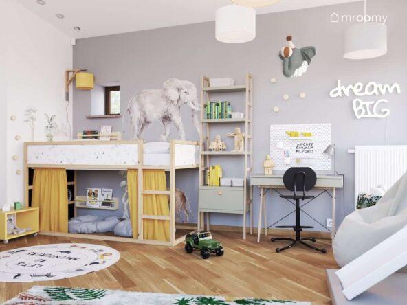 Drewniane łóżko regał z drewnianym stelażem oraz biurko z organizerem a także liczne ozdoby ścienne w pokoju dla chłopca z szarą ścianą