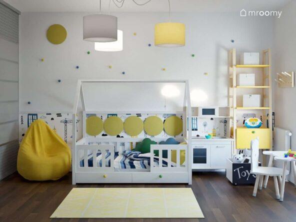 Jasny pokój dla chłopca z łóżkiem w kształcie domku żółtymi dodatkami oraz ścianą ozdobioną gałkami w różnych kolorach i tapetą z motywem budowy