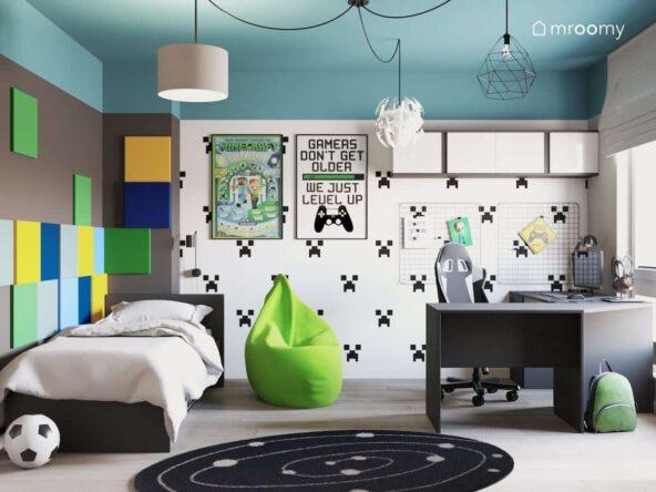 Pokój dla nastolatka fana gier komputerowych z wygodnym narożnym biurkiem okrągłym czarnym dywanem czarno-białą tapetą plakatem Minecraft zielonym workiem sako kwadratowymi piankowymi panelami na ścianie w kolorach żółtym błękitnym granatowym i zielonym lampą typu pajączek z różnymi abażurami