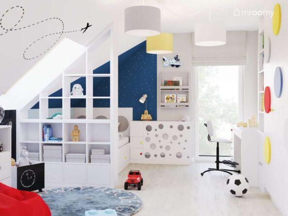 Poddaszowy pokój dla chłopca w jasnych kolorach z lampa sufitową z trzema abażurami naklejką ścienną oraz lampką nocną w kształcie samolotu i niebieskim dywanem z alfabetem