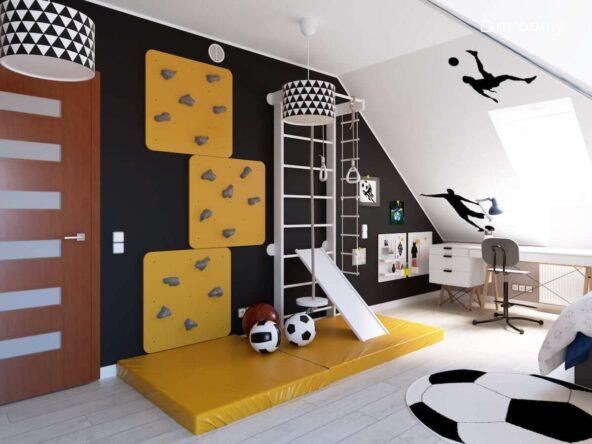 Czarna ściana z drabinką gimnastyczną żółtą ścianką wspinaczkową i organizerami ściennymi a u sufitu lampy z abażurami w trójkąty w poddaszowym pokoju dla chłopca