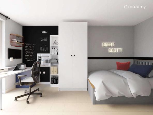 Biała szafa duże łóżko wysoki regał oraz ledon w kształcie napisu i ściana pomalowana czarną farbą tablicową w pokoju dla nastolatka