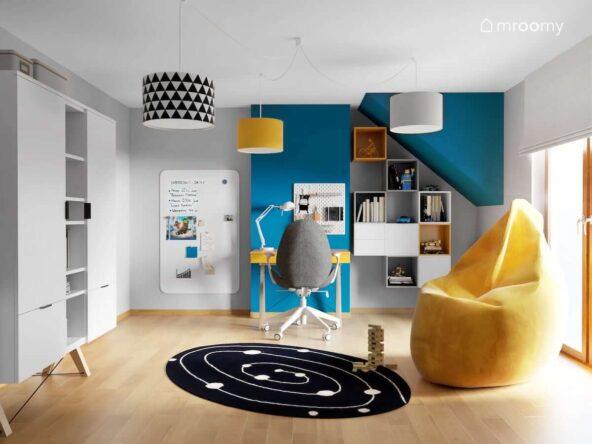 Białe i niebieskie ściany w pokoju dla chłopca z żółtą pufą sako licznymi szafkami ściennymi oraz dużą tablicą magnetyczną