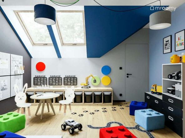 Pokój dla przedszkolaków na poddaszu z niskim regałem z wysuwanymi pojemnikami na zabawki stolikiem do zabawy i krzesełkami z oparcie w kształcie kotka i zajączka okrągłymi panelami ściennymi pełniącymi funkcję dekoracyjną kolorowymi pufkami w kształcie klocków lego sufitową lampą typu pająk z abażurami w różnych kolorach
