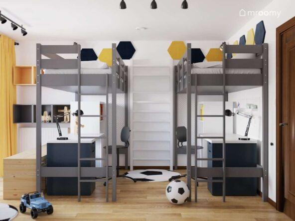 Łóżka na wysokich antresolach a pomiędzy nimi drabinka gimnastyczna a ściany ozdobione miękkimi panelami ściennymi w pokoju dwóch braci