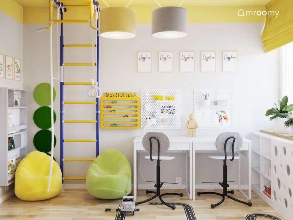 Dwa biurka drabinka gimnastyczna kolorowe pufy a na ścianie półka na samochody oraz organizery ścienne w pokoju dla dwóch chłopców z żółtym sufitem i białymi ścianami