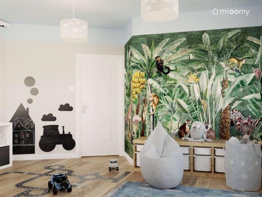 Piękna tapeta w żywych kolorach ze zwierzętami oraz drewniane regały z pojemnikami na zabawki szara pufa sako i tablice kredowe w kształcie domku i traktora w pokoju dla rodzeństwa
