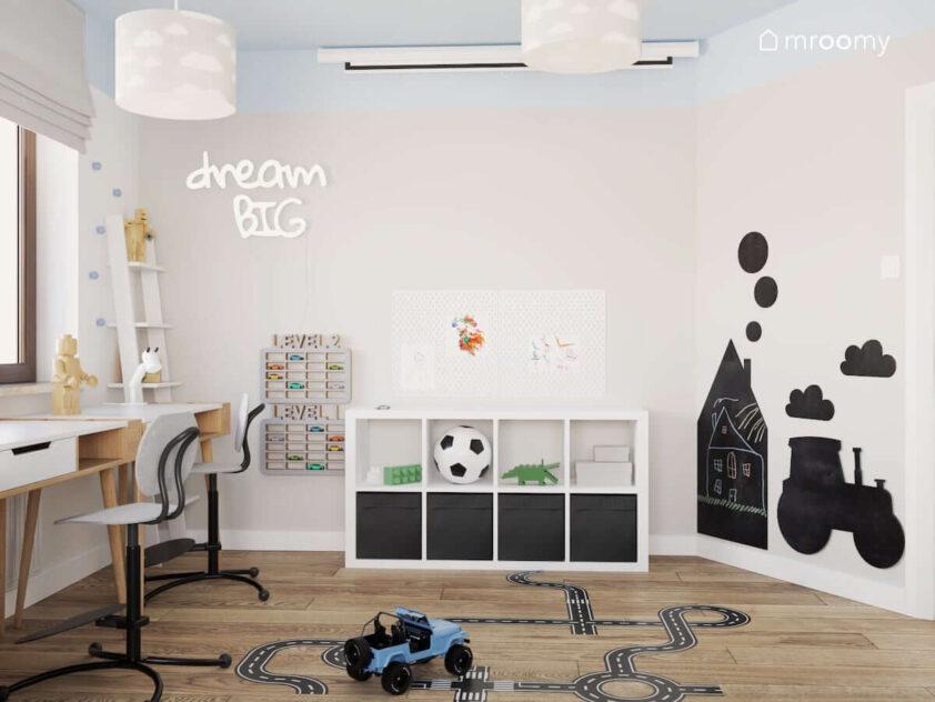 Tablice kredowe w różnych kształtach półki na samochody oraz biało czarny regał a także kinkiet w kształcie napisu a na podłodze naklejka w kształcie jezdni w pokoju dla dwóch braci
