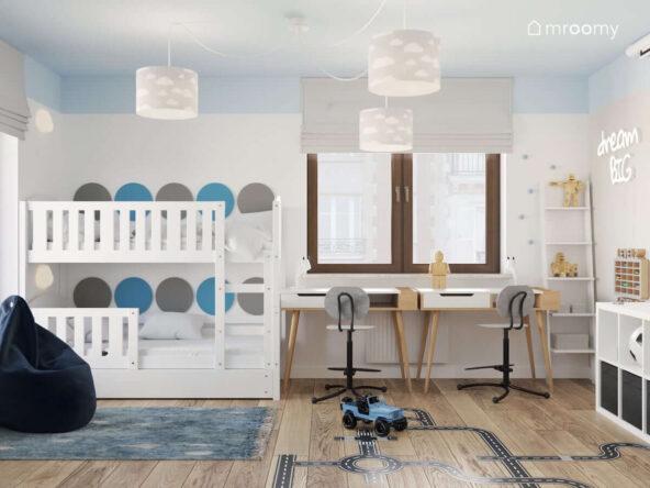 Biało niebieski pokój dla rodzeństwa z białym łóżkiem piętrowym oraz drewnianymi biurkami i lampą sufitową z szarymi abażurami w chmurki