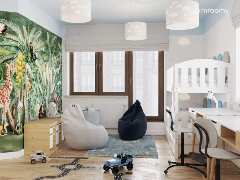 Pokój dla dwóch chłopców z łóżkiem piętrowym drewnianymi biurkami i regałem z pojemnikami na zabawki oraz pufami sako i niebieskim dywanem