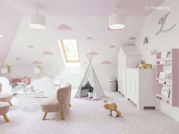 Dziewczęcy pokój dla bliźniaczek na poddaszu w kolorystyce biało-różowej z łóżkami w kształcie chmurki namiotem tipi jasnoróżową wykładziną na podłodze sofą i fotelikami dla dzieci stolikiem z miejscem do przechowywania