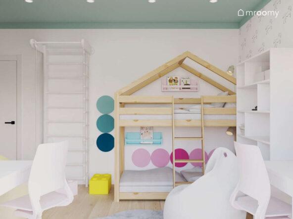 Pokój z seledynowym sufitem łóżkiem piętrowym typu domek dla dwóch sióstr z drabinką gimnastyczną kolorowymi panelami ściennymi w odcieniach różu i turkusu oraz pufką w kształcie klocka lego białym workiem sako i białym regałem na książki