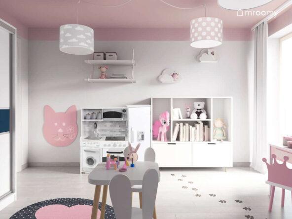 Przestronny pokój na małej dziewczynki w kolorystyce szaro-różowej z białymi meblami czarno-różowym dywanem tablicą suchościeralną w kształcie królika i stoliczkiem z krzesełkami