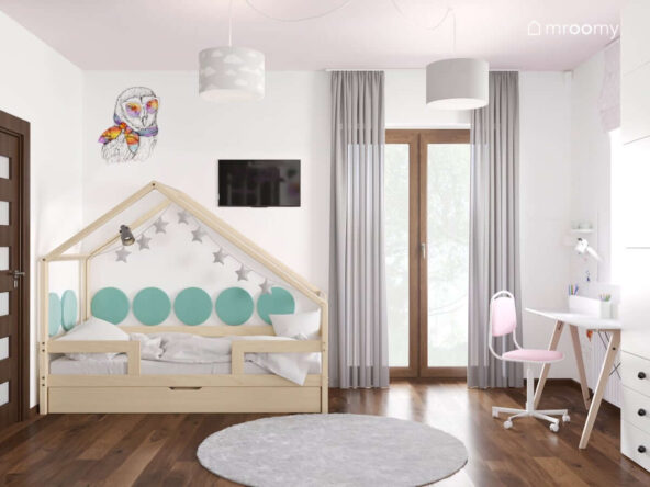Łóżko domek ozdobione miękkimi panelami ściennymi oraz girlandą gwiezdną do tego szare zasłony i dywan a na ścianie naklejka z sową w pokoju sześcioletniej dziewczynki
