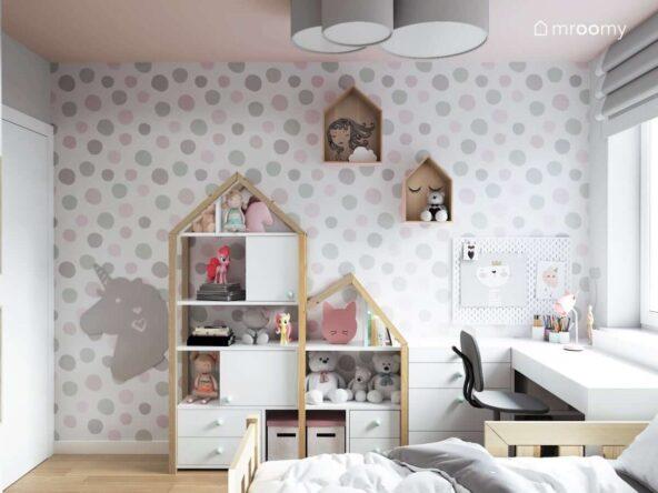 Pokój dla dziewczynki z tapetą w szare i różowe grochy tablicą kredową w kształcie jednorożca regałami w kształcie domków białym biurkiem i szarym krzesłem obrotowym z podnóżkiem  lampą składającą się z trzech szarych plafonów półkami dekoracyjnymi w kształcie domków
