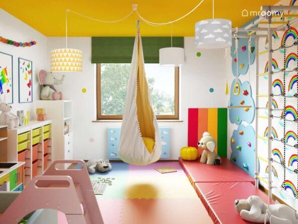 Kolorowy pokój zabaw ze ścianką do wspinaczki huśtawką basenem z kulkami i różową zjeżdżalnią piankowymi panelami ściennymi w kolorach tęczy żółtym sufitem i zieloną roletą rzymską