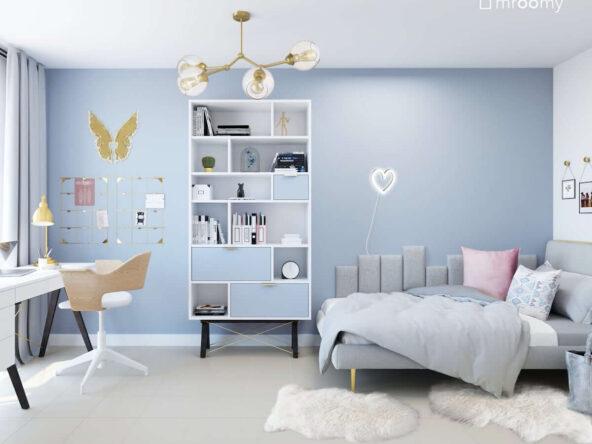 Jasny pokój dla nastolatki w niebieskich kolorach toaletką pojemnym regałem oraz szarym łóżkiem uzupełnionym miękkimi panelami ściennymi a na ścianach ozdobne organizery oraz ledon w kształcie serca