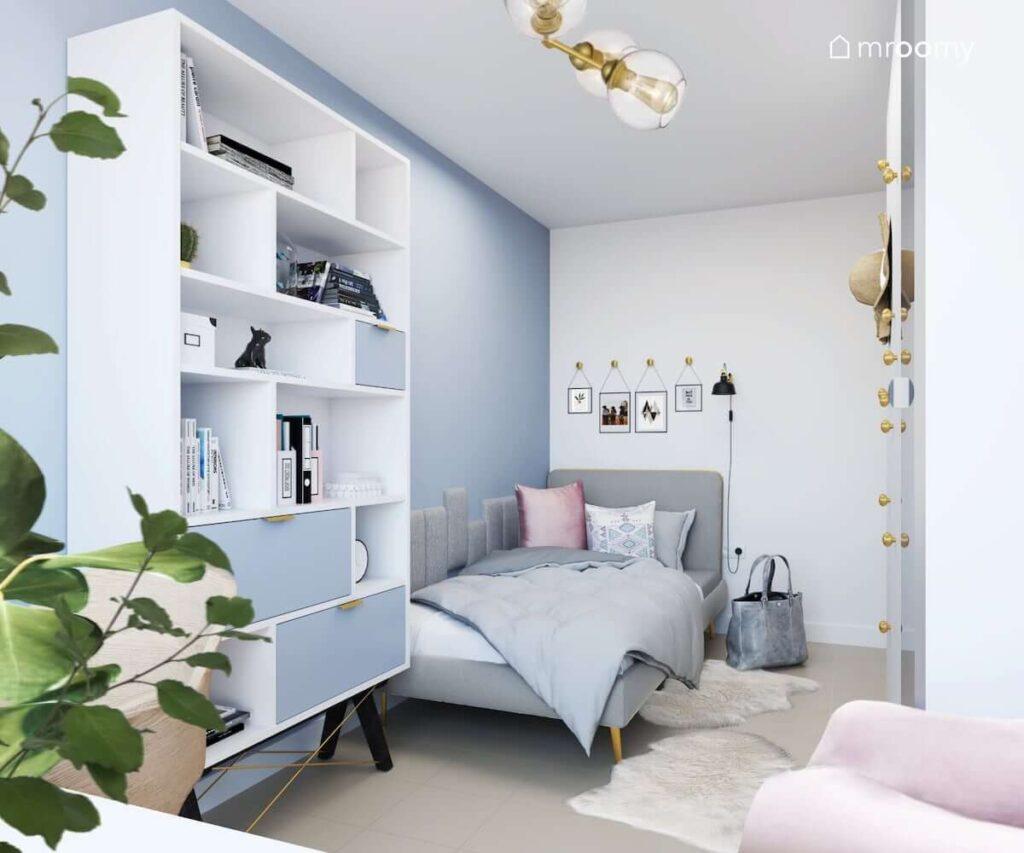 Łóżko duży regał oraz miękkie białe dywany a na niebieskiej ścianie obrazki zawieszone na ozdobnych złotych wieszakach w pokoju dla nastolatki