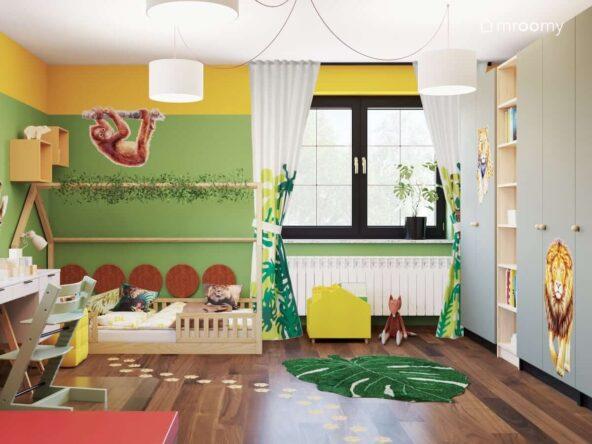 Kolorowy pokój dla dziewczynki z licznymi motywami dżungli oraz drewnianym łóżkiem w kształcie domku i dużymi szafami