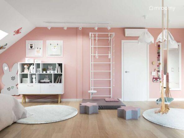 Biało różowy pokój ze skosami dla kilkuletniej dziewczynki z drabinką gimnastyczną tablicą kredową w kształcie królika i białym regałem oraz białymi dywanami i pufkami w kształcie gwiazdek na podłodze