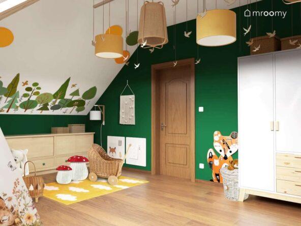 Leśny pokój dla noworodka na poddaszu ze ścianami w kolorze butelkowej zieleni ozdobionymi naklejkami przedstawiającymi las i jego mieszkańców z żółtymi dodatkami lampami bambusowymi tablicą manipulacyjną w kształcie liska i pojemnikami na zabawki w kształcie muchomorka