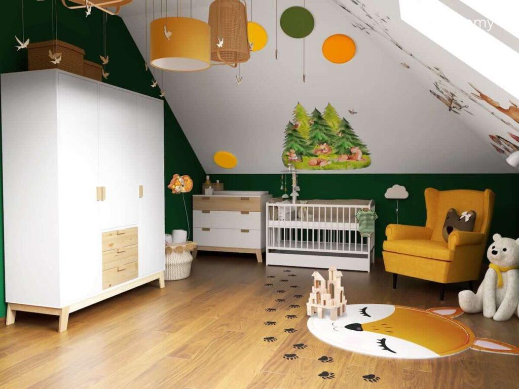 Pokój dla niemowlaka w stylu woodland z dekoracjami przedstawiającymi las i jego mieszkańców z białymi meblami z elementami drewna z żółtym fotelem typu uszak piankowymi panelami ściennymi i ścianą w kolorze butelkowej zieleni