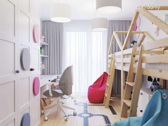 Mały pokój dla rodzeństwa z dwoma biurkami łóżkami na drewnianych antresolach oraz pufami sako a także dużą szafą ozdobioną panelami ściennymi w różnych kolorach