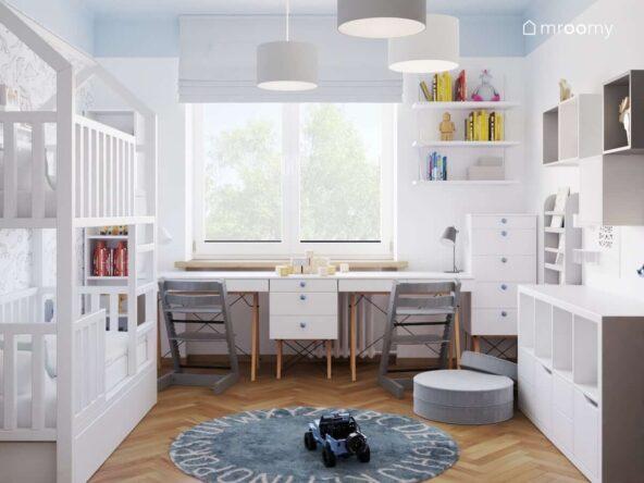 Jasny pokój dla rodzeństwa z biurkami skandynawskimi ustawionymi pod oknem z krzesłami dostosowanymi do wzrostu dziecka lampą sufitową typu pajączek i okrągłym dywanem z alfabetem łóżkiem piętrowym i białymi meblami komodą z niebieskimi gałkami