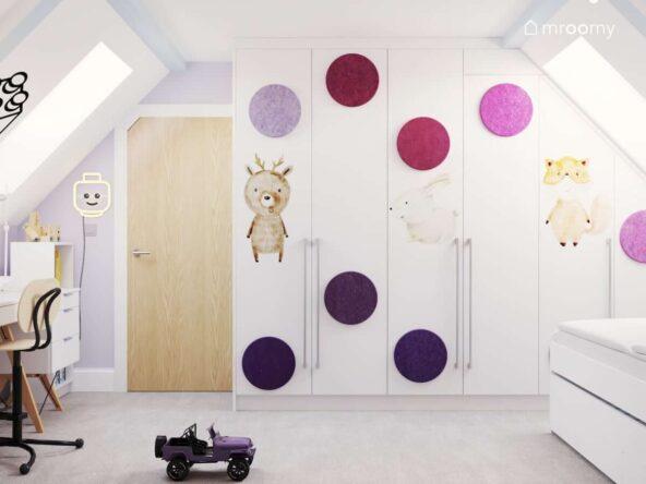 Duża biała szafa ozdobiona naklejkami w kształcie zwierząt oraz miękkimi panelami w różnych odcieniach różu oraz fioletu oraz kinkiet w kształcie głowy ludzika Lego w jasnym pokoju dwóch sióstr na poddaszu