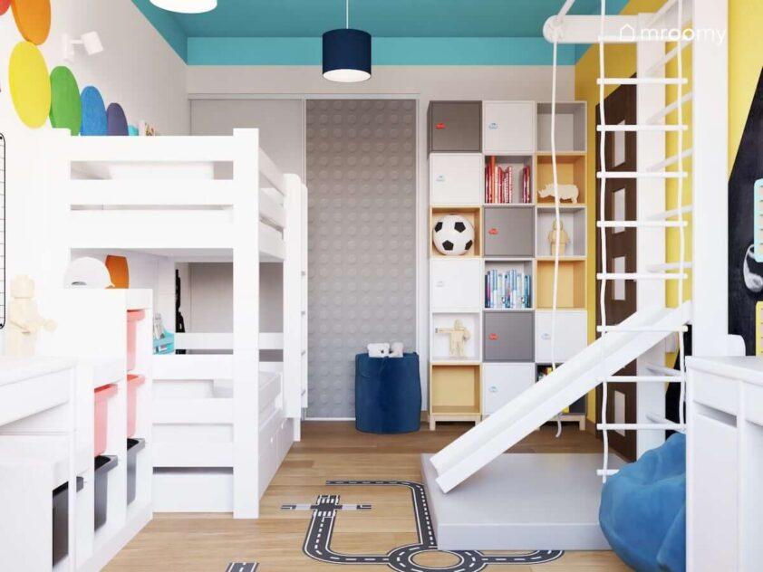 Biało niebiesko żółty pokój dla rodzeństwa z łóżkiem piętrowym licznymi szafkami ściennymi oraz szafą ozdobioną naklejką przypominającą wzór na klockach Lego