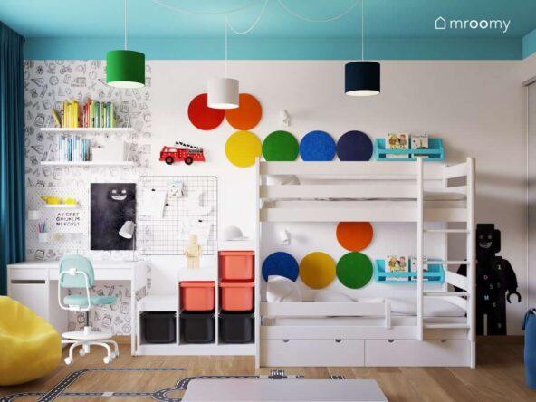 Białe łóżko piętrowe regał z pojemnikami na zabawki oraz biurko a nad nim półki oraz organizery ścienne a na ścianie miękkie panele w tęczowych kolorach w pokoju dla dwóch chłopców