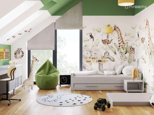 Biało zielony pokój dla chłopca z tapetą z dzikimi zwierzętami białymi meblami oraz zieloną pufą sako i dywanem w łapki