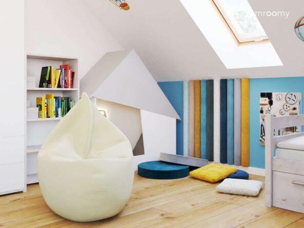 Pokój dla kilkuletniego chłopca z kolorowymi siedziskami w różnych kształtach i kolorach oraz panelami ściennymi w podobnych odcieniach oraz biało szarą kryjówką wyciszającą