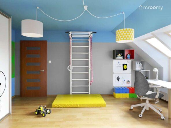 Biało szaro niebieski pokój dla chłopca z drabinką gimnastyczną i żółtym materacem kolorowymi pojemnikami na klocki oraz tablicami magnetycznymi a na suficie lampy na ozdobnym zawieszeniu