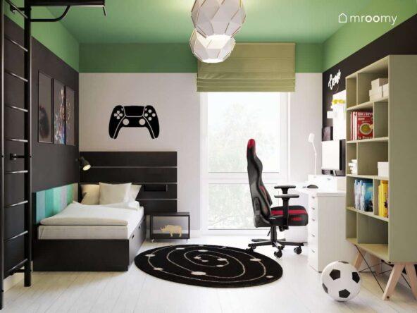 Zielono biało czarny pokój dla fana gier komputerowych z łóżkiem z dużym funkcjonalnym zagłówkiem i naklejką w kształcie pada na ścianie a także czarno białym dywanem i ozdobnymi lampami sufitowymi