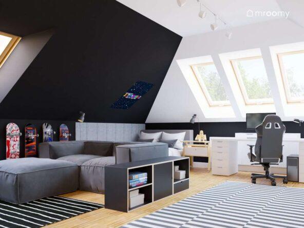 Pokój dla nastolatka utrzymany w stonowanych kolorach z łóżkiem oraz szarą sofą a także biurkiem i regałem ze sklejki i ścianą ozdobioną szarymi panelami ściennymi oraz deskorolkami