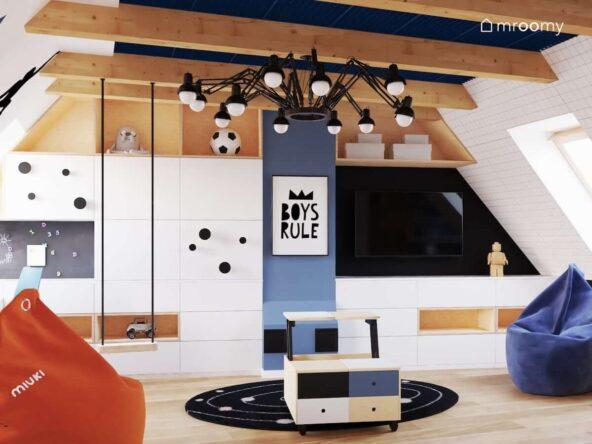 Poddaszowy duży pokój dla dwóch chłopców z biało drewnianymi meblami huśtawką zawieszoną na belce sufitowej oraz oryginalną czarną lampą sufitową