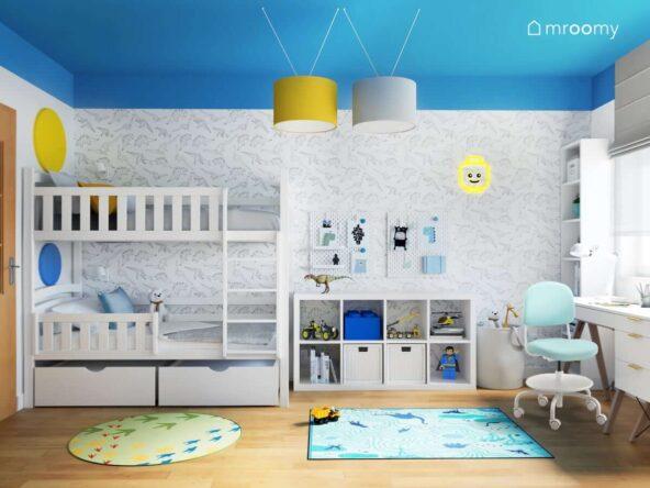 Pokój dla dwóch braci z białym piętrowym łóżkiem oraz białymi regałami i biurkiem a także tapetą i dywanami w dinozaury