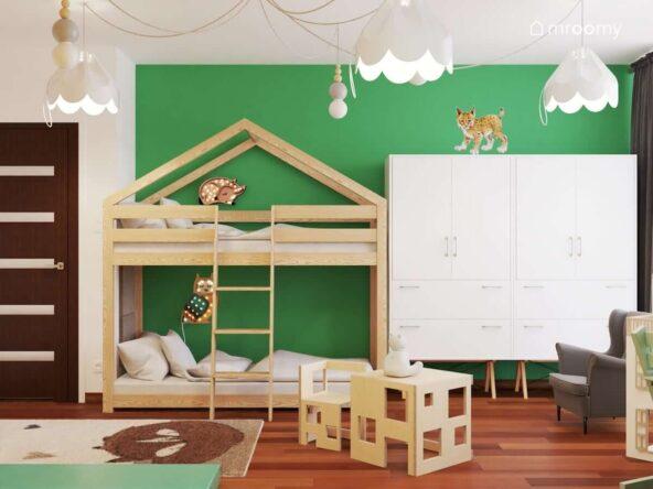 Drewniane łóżko piętrowe w kształcie domku z lampkami nocnymi w kształcie sarny i sowy oraz biała szafa a na suficie ozdobne lampy na rozłożystym zawieszeniu w pokoju dla rodzeństwa z białymi i zielonymi ścianami